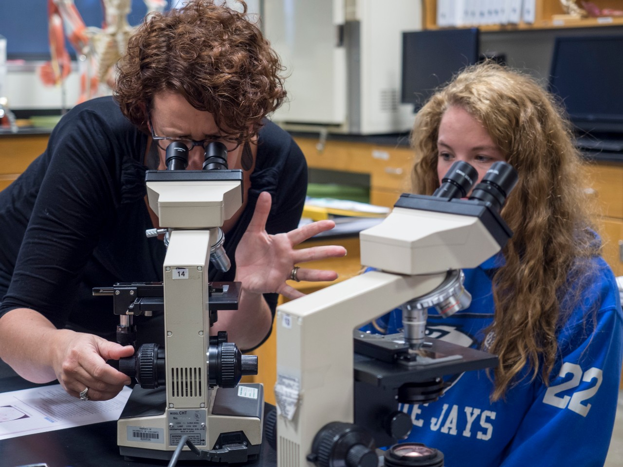 Krista Clark using microscope with student
