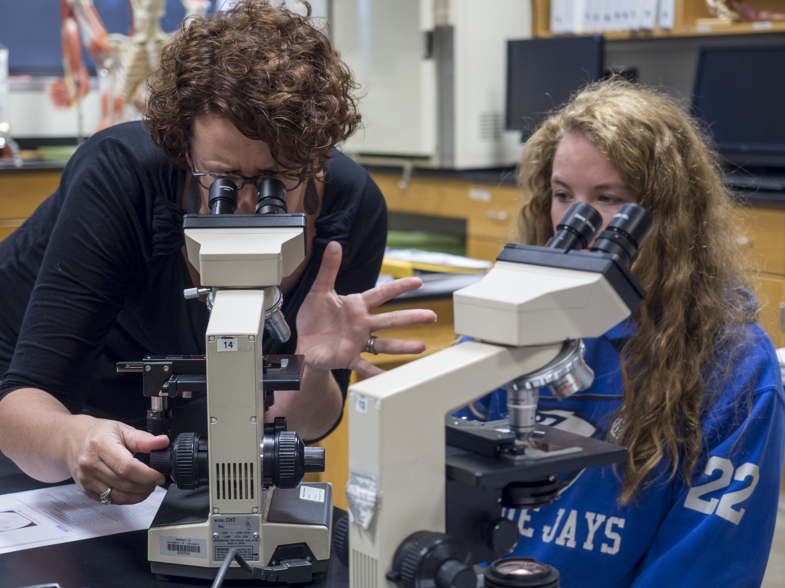 Krista Clark using microscope with student