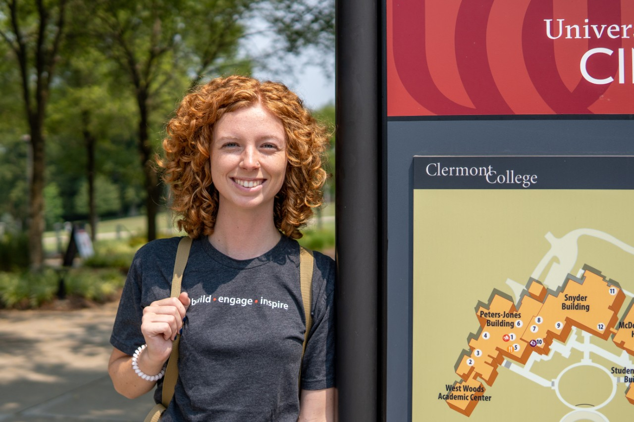 Girl standing by UC Clermont sign and campus map