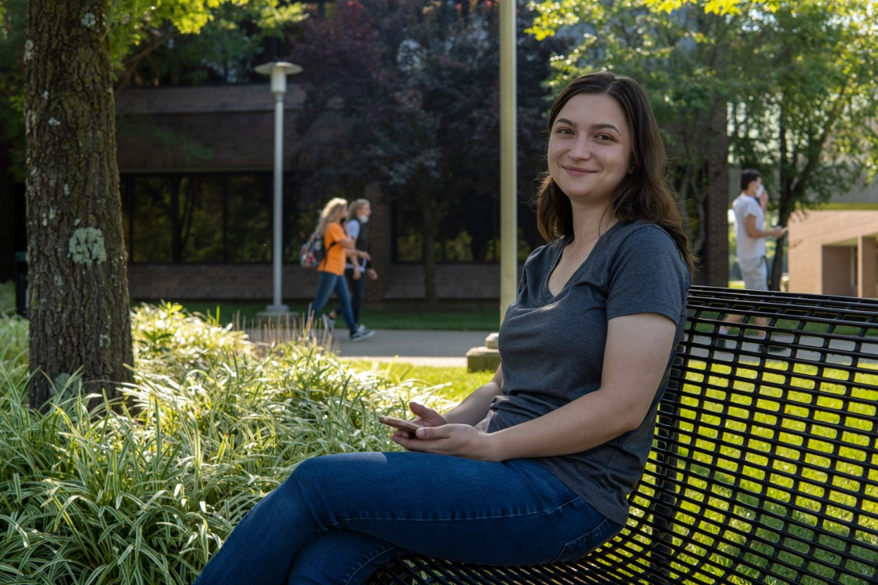 student sitting on bench on campus